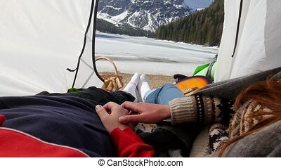 Young couple lying in the tent. Mid shot