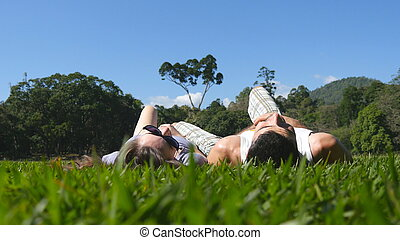 Young couple lying on green grass in park and relaxing. Man and woman sitting on meadow at nature and kissing. Girl and boy looking at the landscape and enjoying vacation. Low angle of view Rear Back