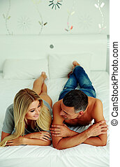 Young couple lying on the bed at home