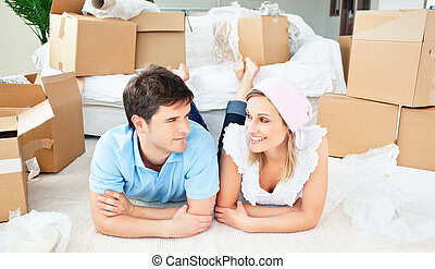 Young couple lying on the floor after unpacking boxes in...