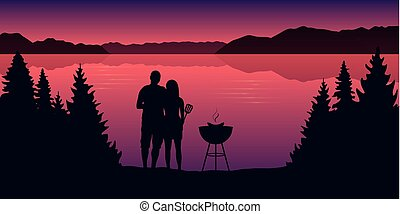 young couple makes a barbeque in the nature landscape by the lake at sunset