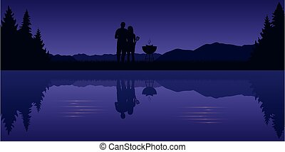 young couple makes a barbeque in the nature landscape by the lake