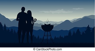 young couple makes a barbeque in the nature landscape with mountain view