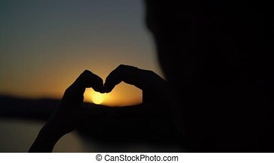 Young couple makes heart from hands on sunset