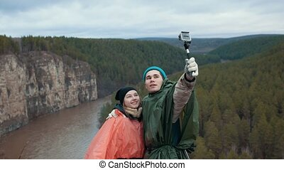 Young couple makes selfie at the hillside on the mountain...