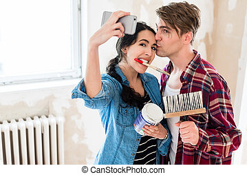Young couple making a selfie while working to the renovation of