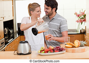 Young couple making fresh fruits juice