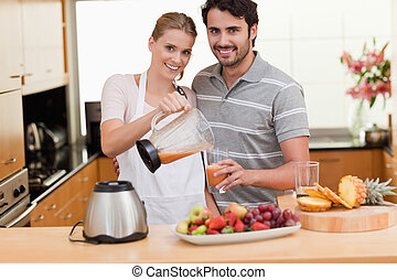 Young couple making fruits juice