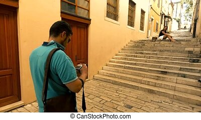 Young couple making photos on narrow Mediterranean street on vacation