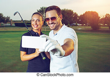 Young couple making selfie on a golf course