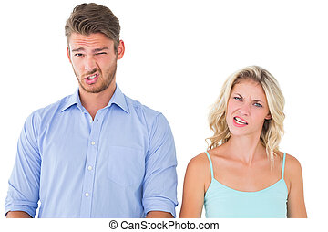 Young couple making silly faces on white background