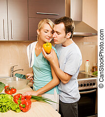 Young couple making vegetable salad in the kitchen
