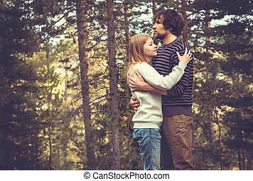 Young Couple Man and Woman Hugging in Love Romantic Outdoor with forest nature on background
