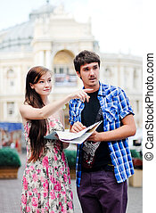 Young couple man and woman looking on map in city centre and showing direction