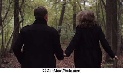 Young couple man and woman running in autumn forest. Slow motion
