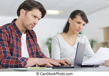 young couple managing finances using laptop