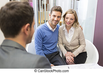 Young couple meeting real-estate agent for house investment