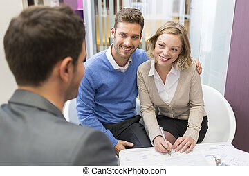 Young couple meeting real-estate agent for house investment. Signing a contract