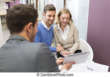 Young couple meeting real-estate showing a house project on a digital tablet .