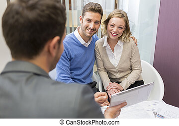 Young couple meeting real-estate showing a investment project on a digital tablet .