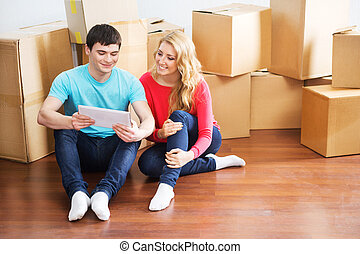 Young couple moving in a new home. Man and woman with a tablet computer.