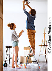 Young couple moving in new house, changing a light bulb.