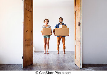 Young couple moving in new house, holding boxes.