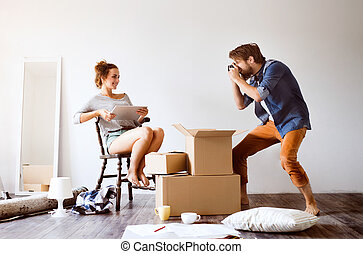 Young couple moving in new house, taking photos.