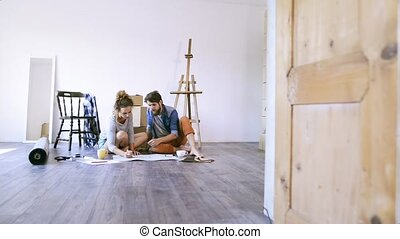 Young couple moving in new house, unpacking things.