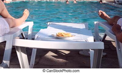 young couple lying beside the swimming pool eating crisps
