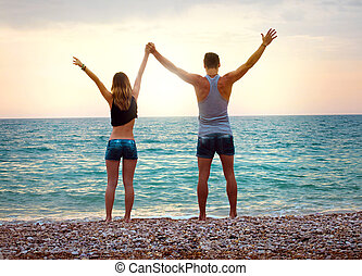 Young couple near the sea at sunset with arms raised