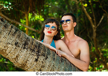 Young couple next to a palm tree in the jungle on a tropical...