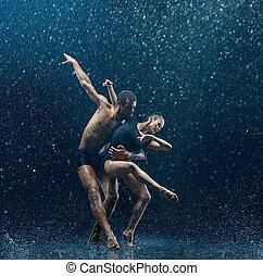 Young couple of ballet dancers dancing unde rwater drops