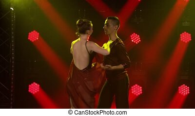 Young couple of dancers dancing ballroom dance elements. Rumba, salsa, tango, flamenco. Dance partners man and woman dance passionately in the dark against the backdrop of red spotlights. Close up