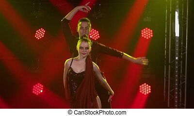 Young couple of dancers dancing ballroom dance elements. Rumba, salsa, tango, flamenco. Dance partners man and woman dance passionately in the dark against the backdrop of red spotlights. Close up. Slow motion.