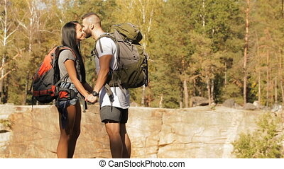 Young couple of hikers kisses near the cliff