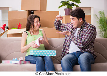 Young couple of man and pregnant wife with giftbox