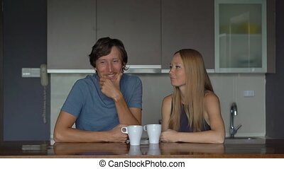 Young couple of man and woman in a kitchen have fun and...
