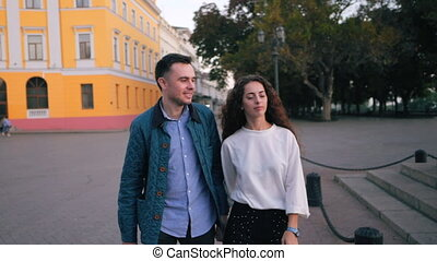 Young couple of man and woman walking in autumn city....