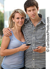 Young couple of students with mobile phone