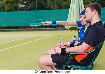 Young couple of tennis players having a rest and watching the game at the tennis court