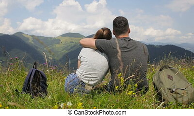 Young couple of tourists are resting in the mountains against the background of clouds