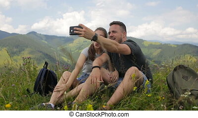 Young couple of tourists doing selfie in the mountains