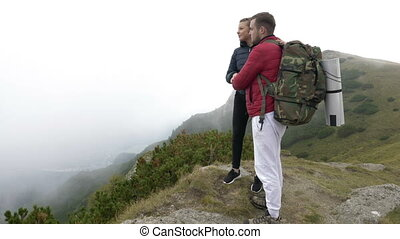 Young couple of tourists kissing on the edge of mountain...
