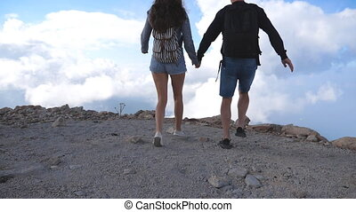 Young couple of tourists with backpacks running to the edge of beautiful canyon and victoriously outstretching arms up. Man and woman reaching up top of mountain and raised hands. Slow motion