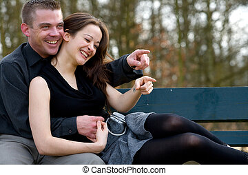 Young couple on a bench having fun - Man and girlfriend on a...