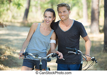 young couple on a bike ride in the forest