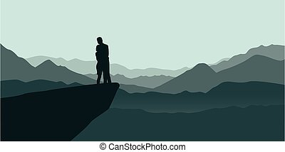young couple on a cliff enjoy the mountain view