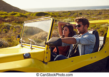 Young couple driving their car on a roadtrip. Handsome young man with his girlfriend on a holiday. Couple on a long drive.
