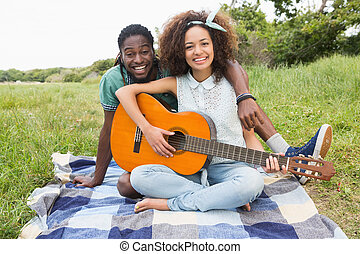 Young couple on a picnic playing guitar